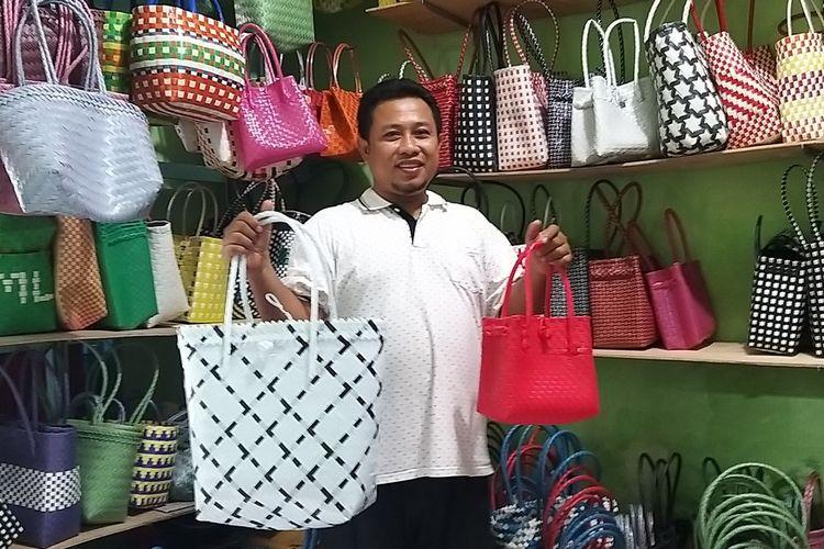 SUKSES--Azhar Budiarso (42), warga Kelurahan Winongo, Kecamatan Manguharjo, Kota Madiun menenteng tas anyaman plastik besutannya. Setelah keluar dari perusahaan telekomunikasi, Budi sukses berjualan tas anyaman plastik hingga ekspor ke luar negeri.