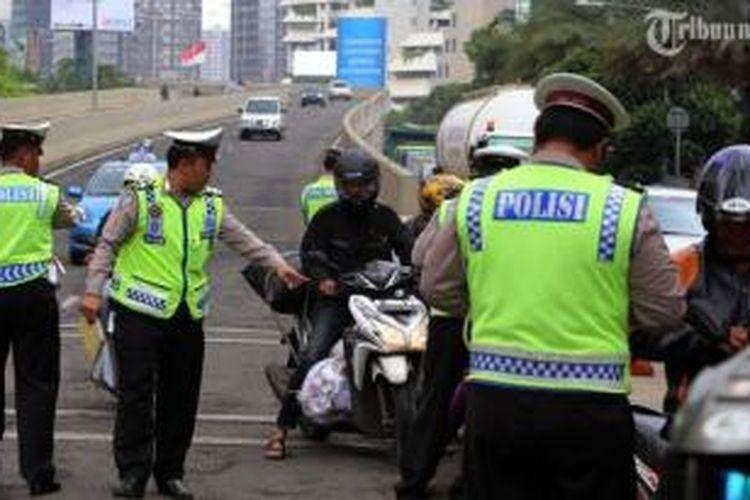 Polisi lalu lintas merazia para pengendara sepeda motor yang nekat melintasi JLNT Kampung Melayu-Tanah Abang di kawasan Karet, Jakarta Pusat, Selasa (28/1/2014). Puluhan pengendara sepeda motor terjaring dalam razia yang dilakukan untuk menekan tingkat kecelakaan. Seharusnya pemotor dilarang melintas JLNT tersebut.