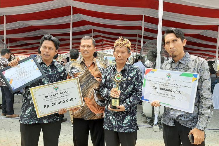 Pelaksana Tugas Kepala Desa Kertayasa, Kabupaten Pangandaran, Jawa Barat, Muhtar Tajidin (membawa piala) membawa piala juara pertama lomba Desa Wisata Nusantara 2019 untuk kategori maju.