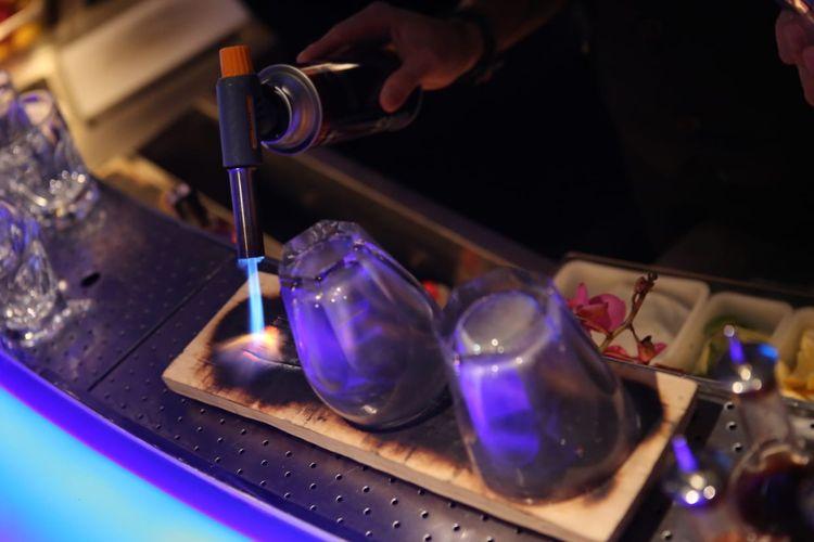 Pembakaran kayu kopi untuk mendapatkan aroma bakar pada gelas yang akan menampung koktain corn and pepper karya Richard Charles dari resto Hakkasan.