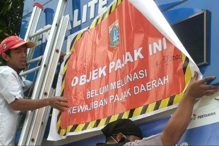 Penyegelan reklame SPBU milik Pertamina di Jalan Yos Sudarso, Tanjung Priok, Jakarta Utara, Kamis (20/2/2020)