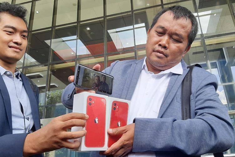 Koordinator MAKI Boyamin Saiman menunjukkan dua unit iPhone hadiah sayembara mencari Harun Masiku dan Nurhadi di Gedung Merah Putih KPK, Jumat (21/2/2020).