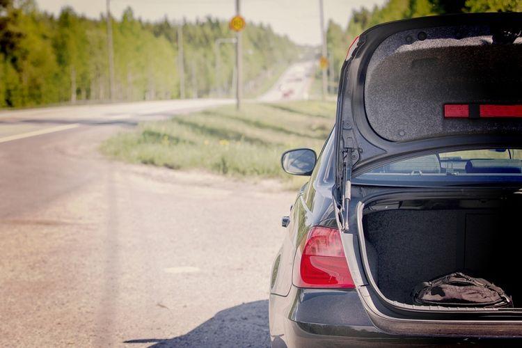 Ilustrasi bagasi mobil di pinggir jalan.