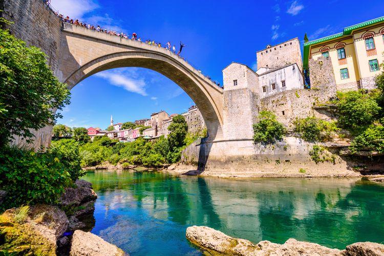 Ilustrasi turis dan pemuda lokal terjun bebas dari Jembatan Stari Most di Mostar, Bosnia dan Herzegovina