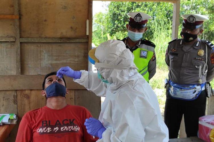 Petugas saat mengambil sampel rapid tes antigen para pengendara yang tidak dapat menunjukkan surat antigen yang masih berlaku di perbatasan Jambi-Sumatera Selatan
