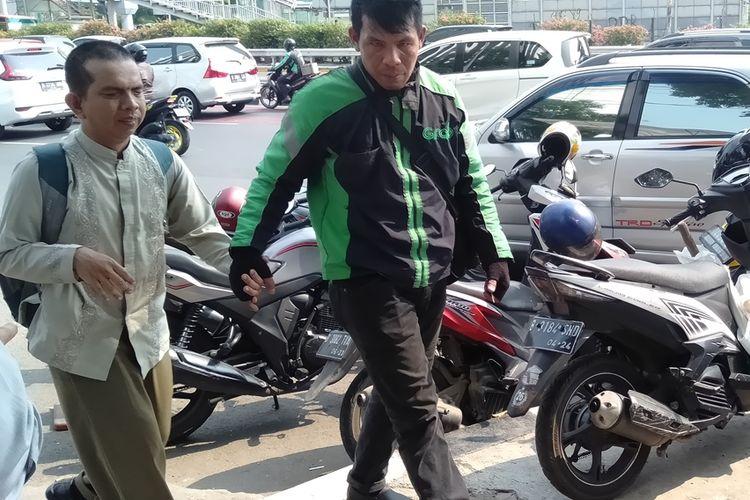 Zulkifli gandeng penumpangnya yang tuna netra ke dalam gedung Kemenaker, Jakarta Selatan, Kamis (31/10/2019)