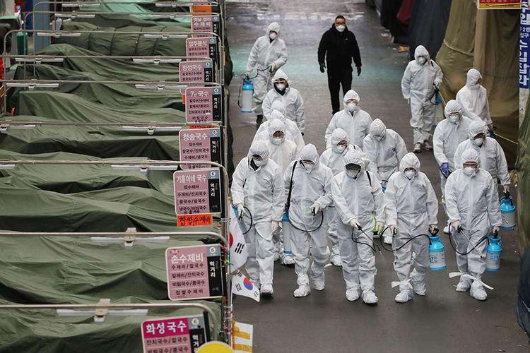 Para petugas dilengkapi pakaian pelindung menyemprotkan cairan desinfektan di sebuah pasar di daerah Daegu, Korea Selatan, menyusul meluasnya wabah virus corona di negara itu, Minggu (23/2/2020). Penyebaran virus corona hingga hari ini, Senin (24/2/2020), semakin menunjukkan peningkatan di sejumlah negara, seperti Italia, Iran, dan Korea Selatan.