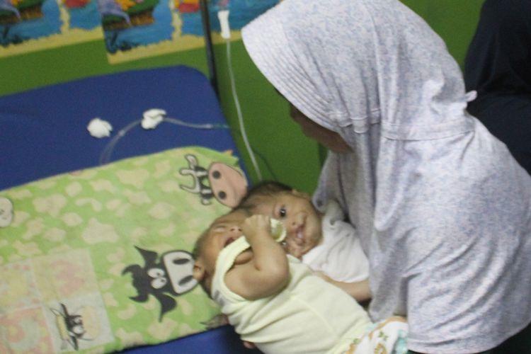 Bayi kembar siam dempet kepala, Fadlan dan Fadli di pangkuan bibinya saat menjalani perawatan medis di IGD RSUD Sayang, Cianjur, Kamis (22/08/2019). Kedua bayi malang itu kini telah dirujuk ke RSHS Bandung guna tindakan medis lanjutan.