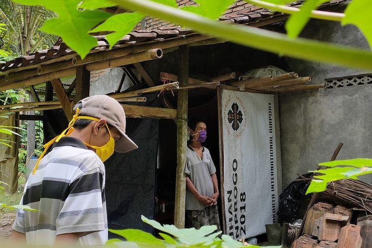 Sakir (62 tahun) pulang dari Berau, Kalimantan Timur, langsung menempati ruang isolasi dari bekas gudang kayu bakar yang berada di samping rumah. Bangunan mungil itu berada di tengah kebun kayu keras, pohon kelapa hingga jati.