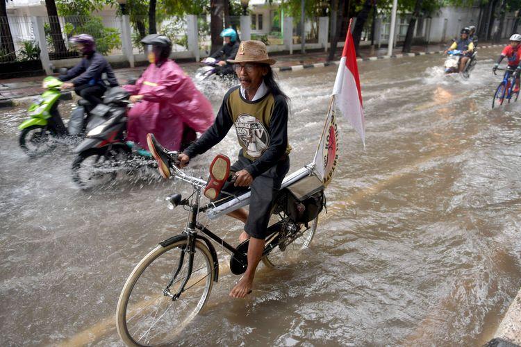Warga melintasi banjir yang merendam Jalan Penataran di Jakarta, Minggu (23/2/2020). Banjir terjadi akibat tingginya intensitas hujan dan buruknya drainase.