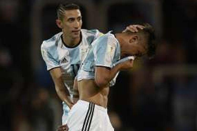 Gelandang Argentina, Angel di Maria (kiri), menenangkan rekan setimnya, Paulo Dybala, yang baru diganjar kartu merah pada laga kontra Uruguay di Mendoza, Argentina, Kamis (1/9/2016) atau Jumat pagi WIB.