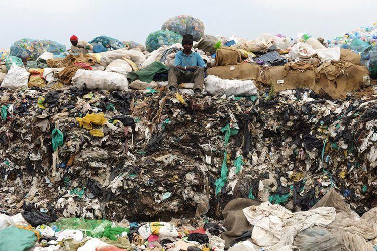 Seorang pria duduk di atas tumpukan sampah di pembuangan kota Ngong, Kenya