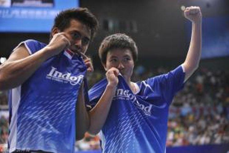 Ganda campuran Indonesia, Tontowi Ahmad (kiri)/Liliyana Natsir, mencium jersey-nya setelah berhasil menjadi juara dunia pada BWF World Championships 2013, di Tian-He Indoor Gymnasium, Guangzhou, China, Minggu (11/9/2013).