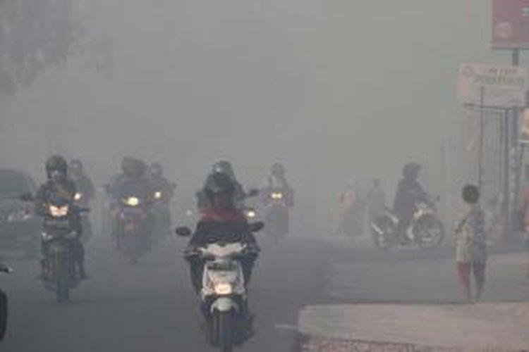 Warga tetap beraktivitas meski kabut asap menyelimuti Kota Pekanbaru, Riau, 20 Juni 2013. Kabut asap berasal dari kebakaran hutan di provinsi tersebut.