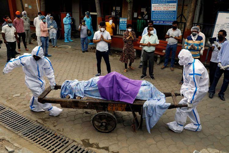 Tenaga kesehatan memakai Alat Pelindung Diri (APD) membawa jenazah seorang warga yang meninggal dunia akibat penyakit virus korona (COVID-19) di sebuah krematorium di New Delhi, India, Rabu (24/6/2020).