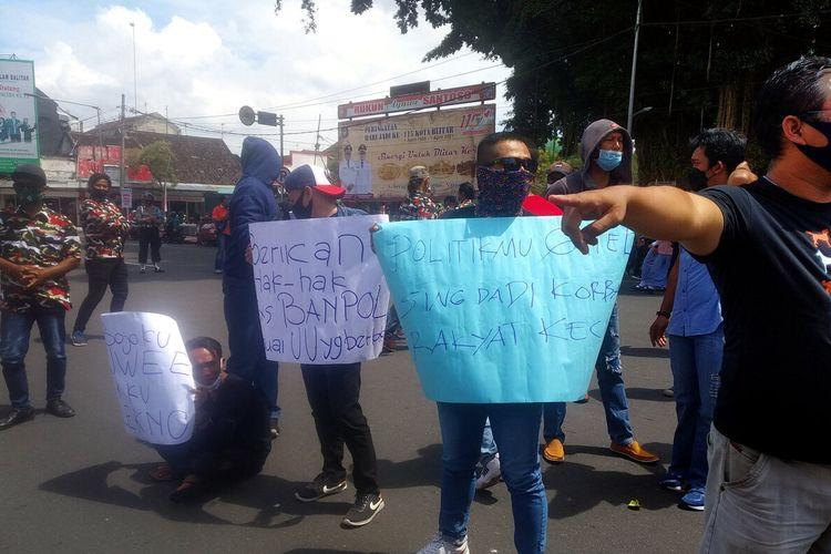 Massa melakukan aksi unjuk rasa memrotes pemutusan kontrak tenaga banpol Satpol PP Kota Blitar di depan Balai Kota Blitar, Senin (29/3/2021)