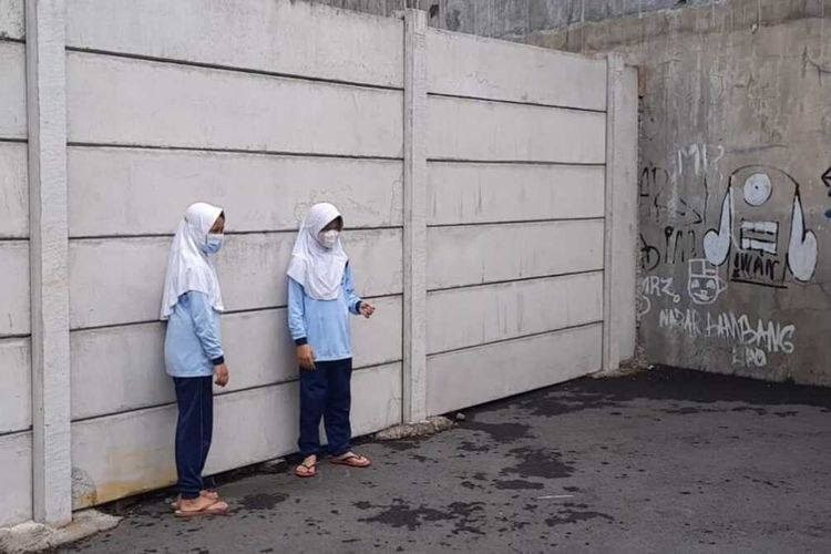 Foto-foto sekolah SD di Kota Tasikmalaya, Jawa Barat, tak punya alses jalan masuk akibat ditutup benteng 3 meter pemilik lahan di depannya dan terpaksa lewati sawah, kuburan dan tebing tinggi bekas Galian C saat diberlakukan PTM Terbatas, Selasa (31/8/2021).