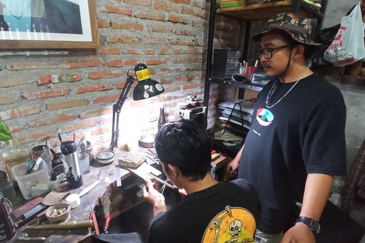Surya (menggunakan topi) saat menunjukkan proses pembuatan cincin perak di workshop miliknya Kotagede, Selasa (23/3/2021)