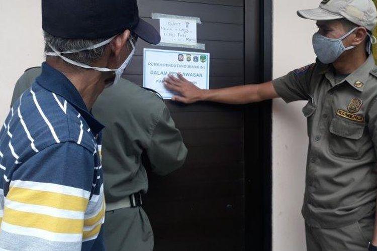 Satpol PP Lenteng Agung menempelkan stiker di pintu rumah warga yang kembali dari kampung halaman, pada Senin (17/5/2021).