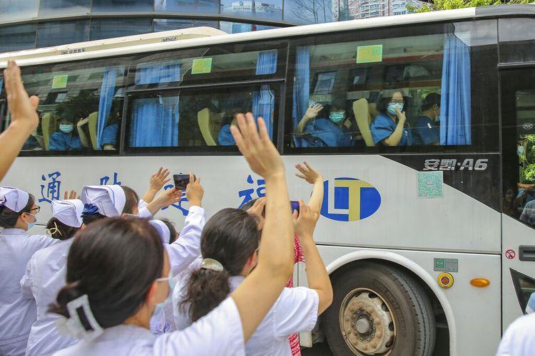 Pekerja medis mengirim rekan mereka pergi untuk membantu dengan wabah COVID-19 di Putian dari sebuah rumah sakit provinsi di Fuzhou di provinsi Fujian China tenggara Minggu, 12 September 2021.