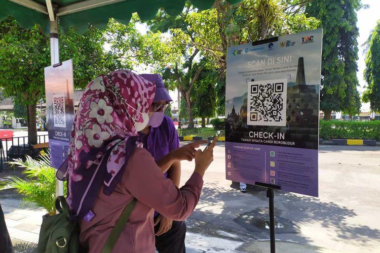 Seorang wisatawan dipandu petugas scan barcode aplikasi PeduliLindungi sebelum masuk Taman Wisata Candi Borobudur Magelang, Jawa Tengah, Jumat (17/9/2021)