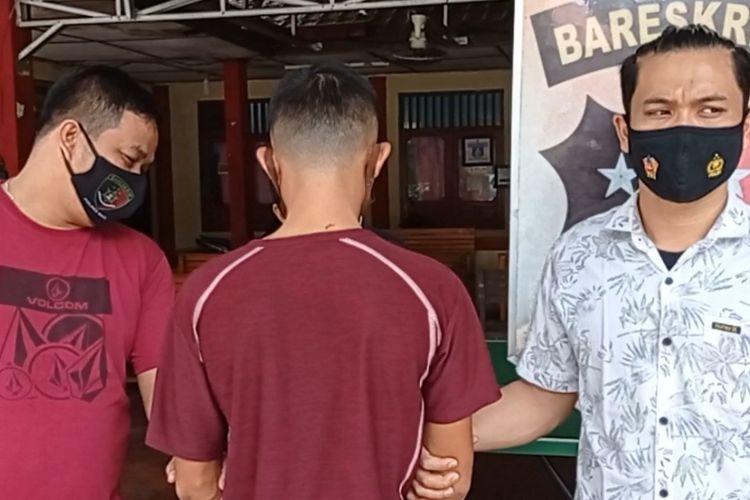 Tersangka pelaku penganiayaan terhadap korban berinisial FZ (12) yang video penganiayaannya viral di media sosial, diapit dua personel Polres Nias.