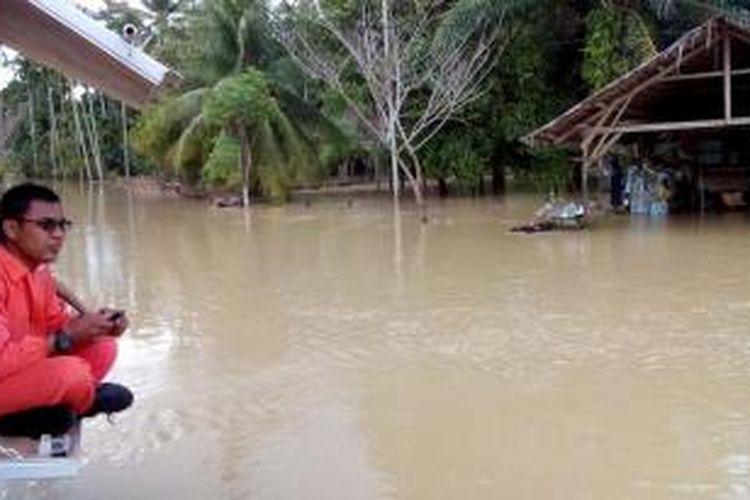 Seorang petugas dari BPBD Aceh Utara sedang memantau kondisi banjir di Desa Parang Sikureung, Kecamatan Matangkuli, Aceh Utara, Minggu (17/1/2016)