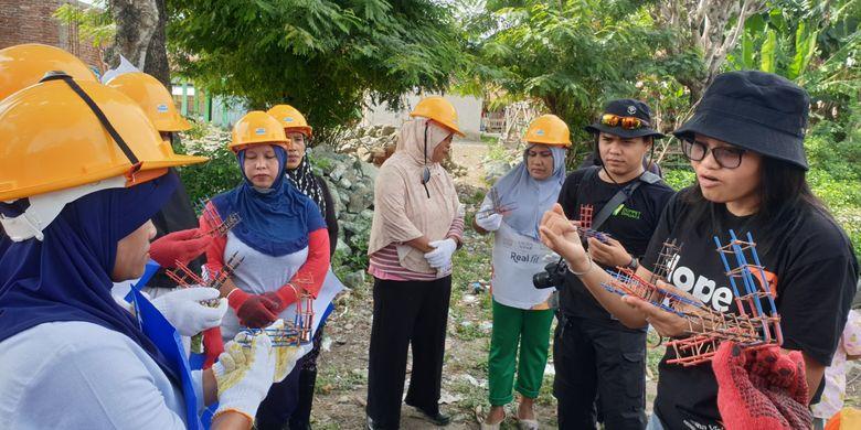 Danni Rossa Wahyuningdita (topi hitam berkacamata) memberikan penjelasan mengenai cara mengikat sambungan besi pondasi dan tiang untuk konstruksi rumah tahan gempa kepada sejumlah ibu-ibu peserta pelatihan Pre-Event Ibu Pelopor Rekonstruksi, 7 Desember 2019.