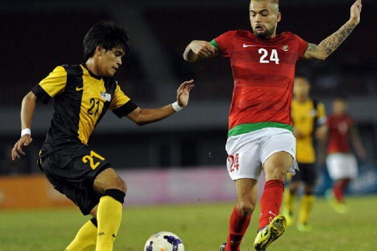Bek timnas Indonesia, Diego Michiels, mencoba menghentikan pergerakan pemain Malaysia pada laga semifinal SEA Games 2013 di Myanmar, 19 Desember 2013.