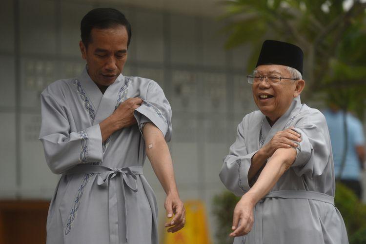 Bakal capres cawapres Pilpres 2019, Joko Widodo (kiri) dan Maruf Amin (kanan) menujukkan bekas pengambilan darah usai pemeriksaan awal tes kesehatan di RSPAD, Jakarta, Minggu (12/8/2018).