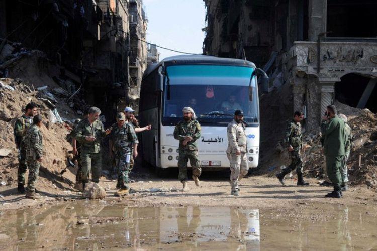 Tentara pasukan yang setia pada Presiden Bashar al Assad terlihat berada di dekat bus yang membawa anggota kelompok pemberontak beserta keluarganya dari kamp pengungsian di Yarmouk di Damaskus, Senin (30/4/2018).