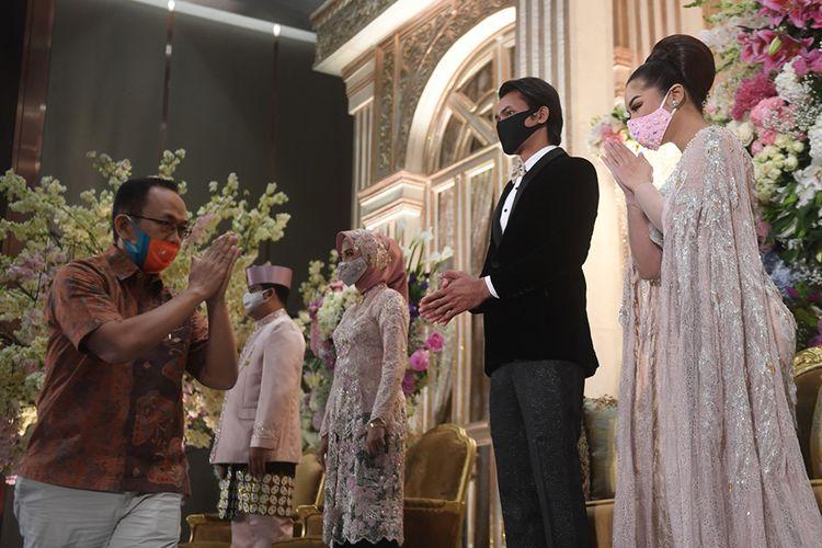 Tamu undangan mengucapkan selamat kepada pasangan pengantin dalam simulasi pernikahan di era normal baru di Jakarta, Kamis (9/7/2020). Simulasi itu dilakukan dengan protokol COVID-19 yang ketat.