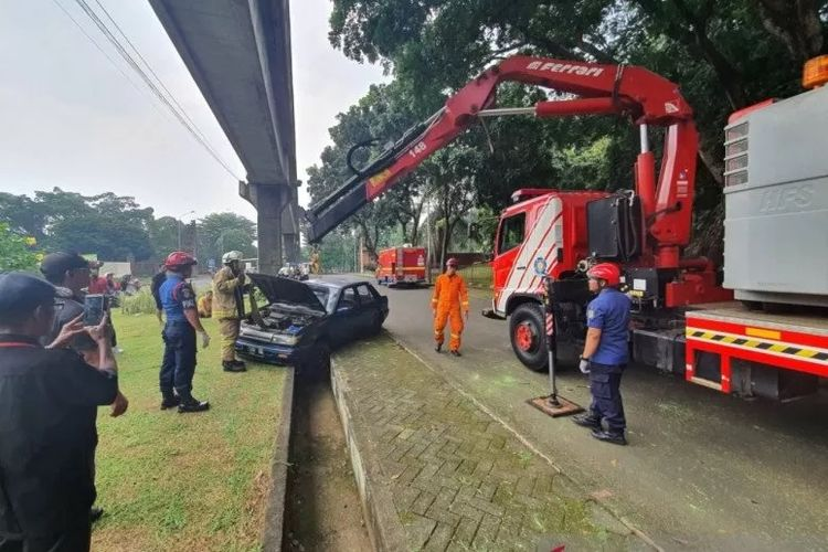 Petugas Damkar Jakarta Timur mengerahkan satu alat berat untuk memindahkan mobil dan pengendaranya yang terperosok di saluran air TMII, Jakarta Timur, Minggu (8/3/2020).