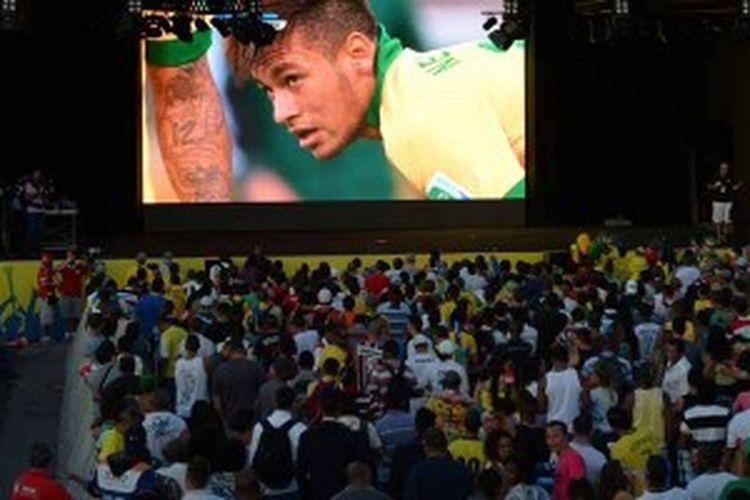 Fans sepak bola menyaksikan aksi striker Brasil, Neymar, saat negaranya melawan Uruguay di semifinal Piala Konfederasi, Rabu (26/6/2013). Brasil menang 2-1 dan lolos ke final, serta laga ini paling banyak menyedot jumlah penonton televisi di seluruh dunia, yang memecahkan rekor untuk Piala Konfederasi.