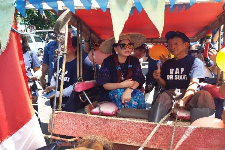 Bupati Minahasa Utara Vonny Anneke Panambunan naik bendi saat mendaftar di Partai NasDem Sulut, Senin (9/12/2019)