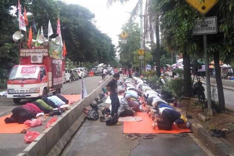 Masaa pendemo sidang kasus dugaan penodaan agama dengan terdakwa Basuki Tjahaja Purnama menunaikan shalat Dzuhur berjamaah di Jalan RM Harsono, Jakarta Selatan, Selasa (31/1/2017).