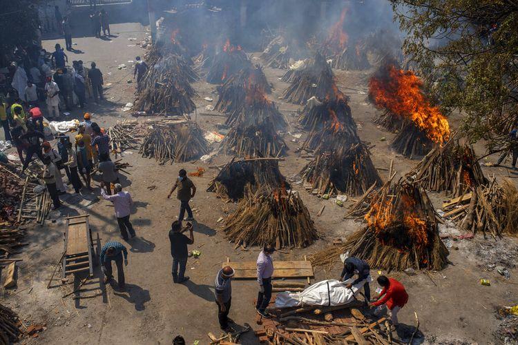 Beberapa tumpukan kayu pemakaman korban Covid-19 dibakar di tanah yang telah diubah menjadi krematorium untuk kremasi massal di New Delhi, India, Sabtu, 24 April 2021. Pihak berwenang India berebut untuk mendapatkan oksigen medis ke rumah sakit tempat Covid-19 pasien tercekik karena persediaan rendah. Upaya pada hari Sabtu dilakukan ketika negara dengan lonjakan virus korona terburuk di dunia mencetak rekor infeksi harian global baru untuk hari ketiga berturut-turut. 346.786 infeksi selama hari terakhir membuat total India lebih dari 16 juta.