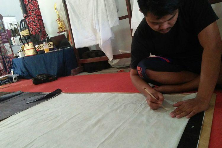 Andri Saprianto (32) owner sekaligus conceptor Deandra Batik Lampung sedang menggambar motif batik di workshop-nya, Rabu (28/10/2020). Dalam satu bulan, Andri bisa menciptakan lebih dari 500 motif batik Lampung