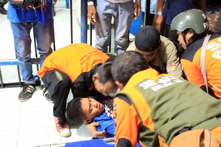Para petugas medis menolong Aremania yang pingsan di Stadion Kanjuruhan seusai laga Arema FC vs Persib Bandung , Minggu (15/4/2018).