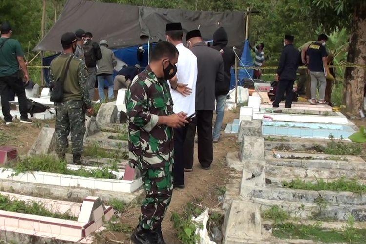 Seejumlah petugas tengah mengamankan proses eksumasi makam DS (22) yang diduga tewas dicekoki garam saat dijadikan tumbal ritual ilmi hitam orangtunya. Kabupaten Gowa, Sulawesi Selatan. Senin, (20/9/2021).
