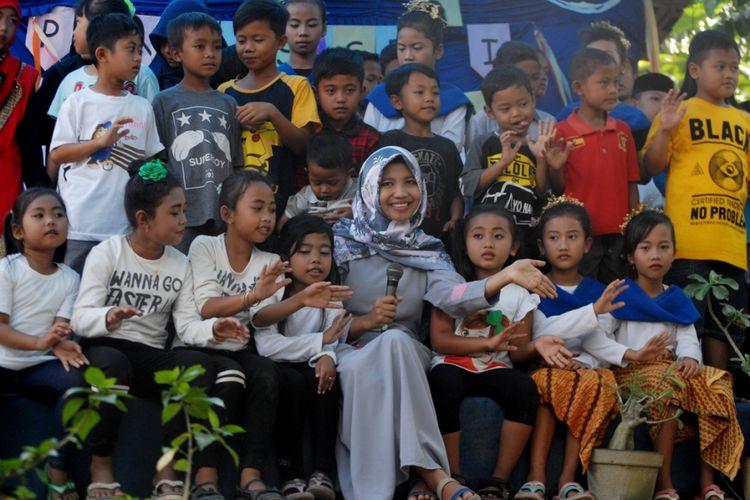 Febri Mustikawati (22), Penggagas Taman Baca Golek Ilmu saat bernyanyi bersama anak-anak dalam acara pentas seni bersama Gramedia di Dusun Welahan, Desa Tambakselo, Kecamatan Wirosari, Kabupaten Grobogan, Jawa Tengah, Minggu (9/7/2017).
