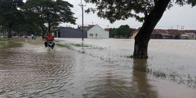 Pengendara sepeda motor yang memaksa melewati jalur Arjawinangun ke Panguragan terendam banjir, Senin (18/1/2021).