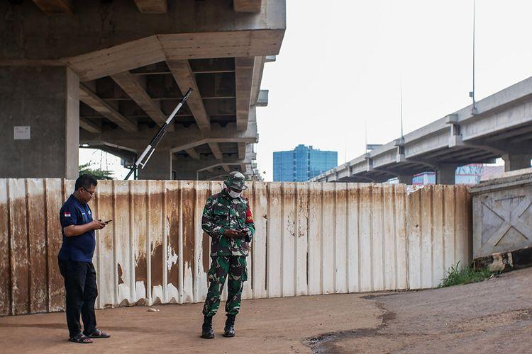 Petugas berjaga di depan pagar penutup RW04 Cipinang Melayu, Jakarta, Minggu (29/3/2020). Untuk mengantisipasi penyebaran COVID-19, masyarakat setempat menutup sebagian akses di wilayah itu karena ada satu warga yang berstatus sebagai Orang Dalam Pemantauan (ODP).