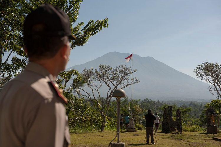 Polisi dan warga memantau aktifitas Gunung Agung di Pos Pemantauan Desa Rendang, Karangasem, Bali, Jumat (15/9). Sejak Kamis (14/9), status Gunung Agung dinaikkan menjadi level waspada menyusul peningkatan aktifitas gunung tersebut sejak bulan Agustus namun hingga kini masih dinyatakan aman.