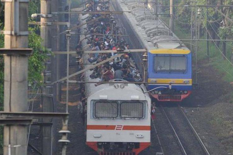 Penumpang memadati atap gerbong kereta rel listrik (KRL) ekonomi Bogor-Jakarta yang melintas di kawasan Tanjung Barat, Pasar Minggu, Jakarta Selatan, Selasa (26/3/2013).