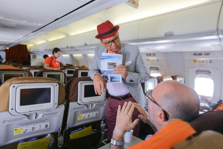 Direktur Niaga Garuda Indonesia, Pikri Ilham Kurniansyah (kiri) berjalan menyapa penumpang Garuda Indonesia dalam penerbangan Jakarta-Balikpapan, Jumat (7/12/2018). Garuda Indonesia meluncurkan layanan penerbangan bernuansa klasik bertajuk Garuda Indonesia Vintage Flight Experience dari tanggal 7-17 Desember 2018