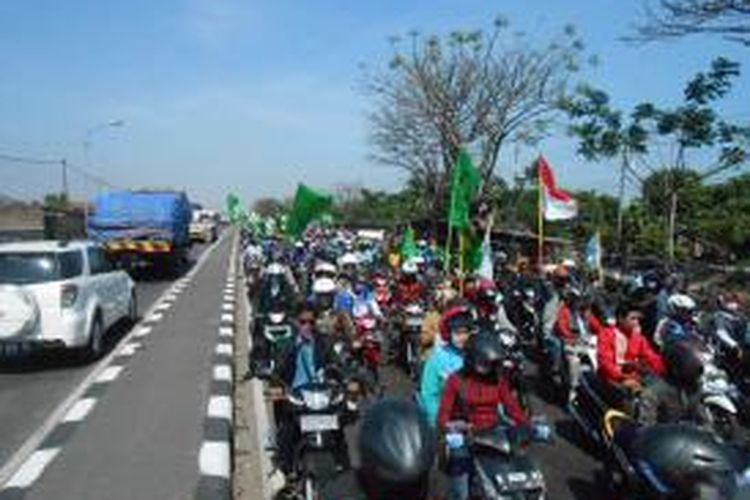 Aksi long march ribuan buruh yang tergabung dalam Gerakan Buruh Demak atau GEBRAK yang menuntut upah layak, memacetkan jalur pantura Demak, Selasa  (24/9/2013)
