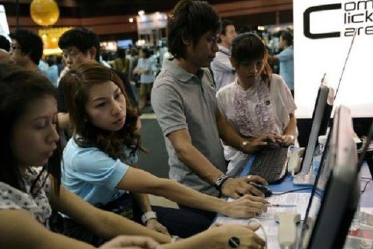 Para pencari kerja melihat iklan lowongan kerja di Bangkok, Thailand.