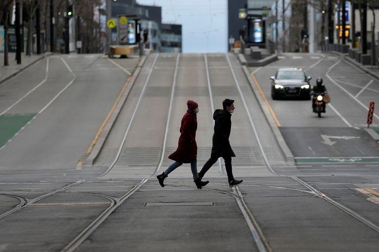 Pejalan kaki berjalan melintasi jalan yang sepi di kota Melbourne, Australia, pada 24 Juli 2021, hari kesembilan lockdown.