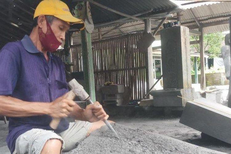 Aep Sudraja (63) sedang memahat batu dengan cara manual, Selasa (13/04/2021).